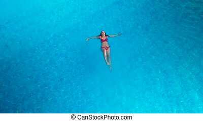 girl floating on her back in the pool