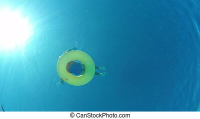 Girl floating on inflatable ring in swimming pool, view from underwater