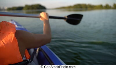 Girl floats in a kayak boat. Slow motion - A girl floats in ...