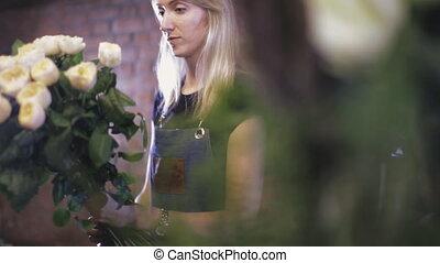 Girl florist makes a bouquet in a floral shop - Close-up....