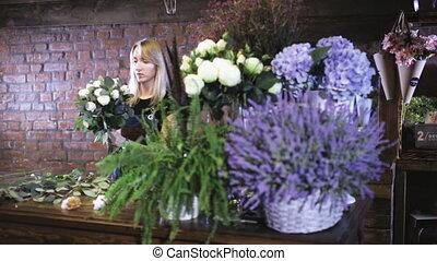 Girl florist makes a bouquet in a floral shop