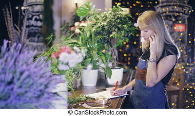 girl florist talking on the phone and writing - female...