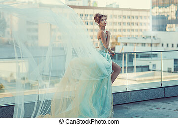 Girl flying fluffy dress. - Young girl standing on the...