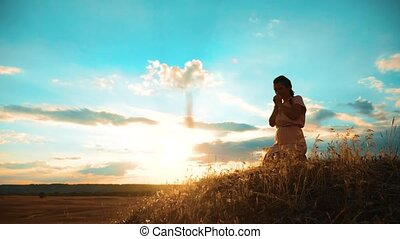 Girl folded her hands in prayer silhouette at sunset. lifestyle woman praying on her knees. slow motion video. Girl folded her hands in prayer pray to God. the girl praying asks forgiveness for sins of repentance. concept Christianity religion catholicism