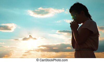 Girl folded her hands in prayer silhouette at sunset. slow motion video. Girl folded her hands in prayer pray to God. girl praying asks forgiveness for lifestyle sins of repentance. believing girl. concept Christianity religion catholicism
