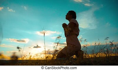 Girl folded her hands in prayer silhouette at sunset. slow motion video. Girl folded her hands in prayer pray to God. girl praying asks forgiveness for sins of repentance. believing girl lifestyle. concept Christianity religion catholicism