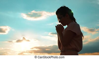 Girl folded her hands in prayer silhouette at sunset. slow motion video. Girl folded her hands in prayer pray to God. girl praying asks forgiveness lifestyle for sins of repentance. believing girl. concept Christianity religion catholicism