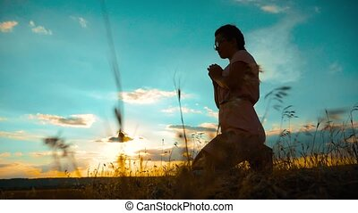 Girl folded her hands in prayer silhouette at sunset. slow motion video. Girl folded her hands in prayer pray to God. girl praying asks forgiveness for sins of repentance. believing girl. lifestyle concept Christianity religion catholicism