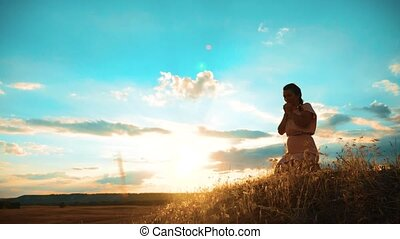 Girl folded her hands in prayer silhouette at sunset. woman praying on her knees. slow motion lifestyle video. Girl folded her hands in prayer pray to God. the girl praying asks forgiveness for sins of repentance. concept Christianity religion catholicism