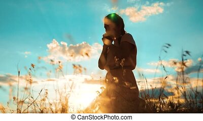 Girl folded her hands in prayer silhouette at sunset. woman praying on her knees. slow motion video. Girl folded her hands in prayer pray to God. the girl praying asks forgiveness for sins of repentance. concept Christianity lifestyle religion catholicism