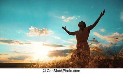 Girl folded her hands in prayer silhouette at sunset. woman praying on her knees. slow motion video. Girl folded her hands in prayer pray to God. lifestyle the girl praying asks forgiveness for sins of repentance. concept Christianity religion catholicism