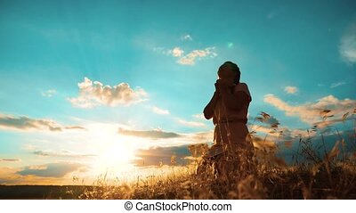 Girl folded her hands in prayer silhouette at sunset. woman praying on her knees. slow motion video. Girl folded her hands in prayer pray to God. the girl lifestyle praying asks forgiveness for sins of repentance. concept Christianity religion catholicism
