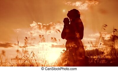 Girl folded her hands in prayer silhouette at sunset. woman...