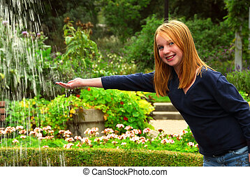 Girl fountain - Young girl holding her hand under falling...