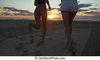 Girl friends running on the beach towards the sea at sunrise
