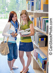 Girl friends studying books together in library