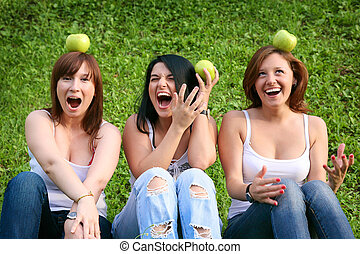 Girl friends with apples in the park