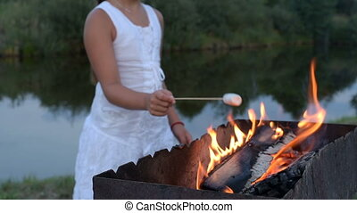 girl fries marshmallows on the fire near the pond -...