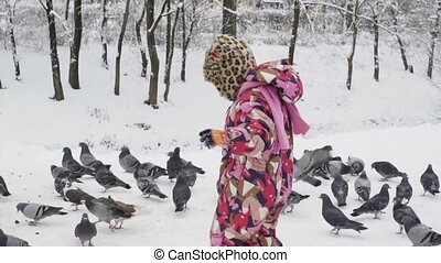 Girl frightens pigeons in the park in winter