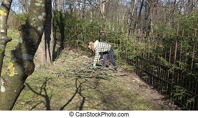 girl gather cut branches in garden yard. Seasonal garden work . 4K
