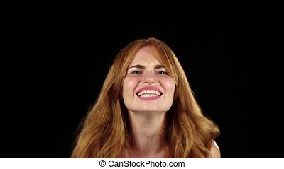 Girl genuinely smile at the camera. Black background. Slow motion