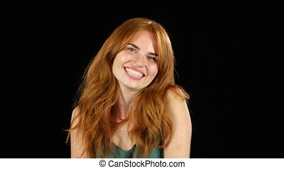 Girl genuinely smile at the camera. Black background - Red...