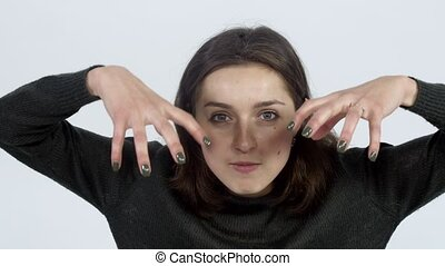 Girl gestures with hands on camera