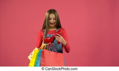 Girl gets a red shoe from the bag and is happy. Pink...