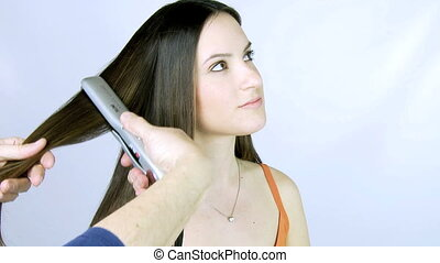 Girl getting her hair ironed