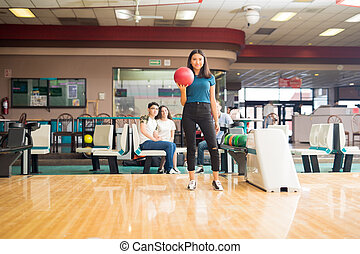 Girl Getting Ready To Throw Bowling Ball In Club