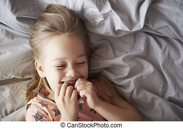 Girl giggling in her bed