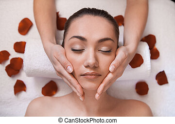 girl given massage on table. gentle face massage with flowers