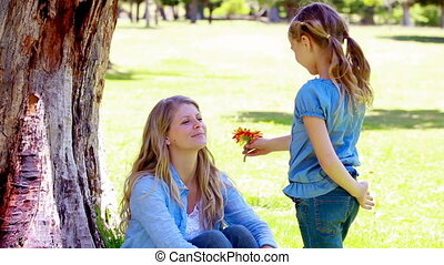 Girl gives a flower to her mother