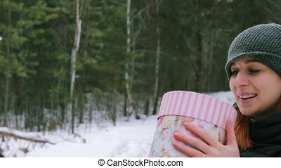 Girl gives a gift in the winter outdoors