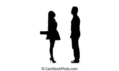 Girl gives a gift to her beloved guy. Silhouette. White...