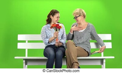Girl gives flowers to her mother. Green screen