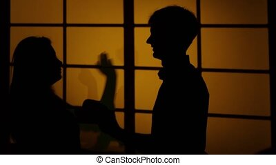 Girl gives the guy a slap in the face. Pushing hands. Silhouette. Close up