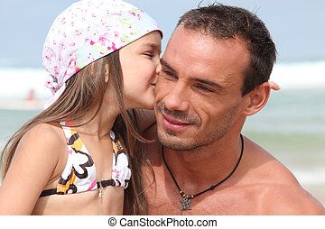 Girl giving dad a kiss