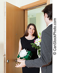 Girl giving flowers and gift to man
