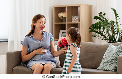 girl giving flowers to her pregnant mother at home