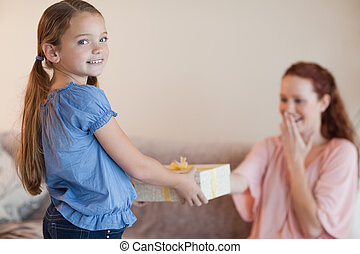 Girl giving her mother a present
