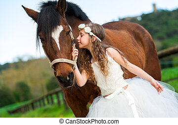 Sweet girl in white dress and flower headband whispering to horse outdoors.