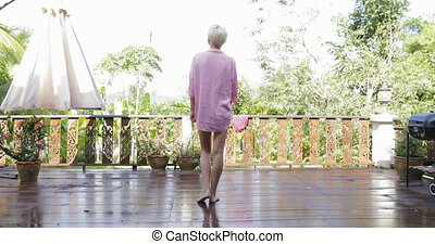 Girl Go Out To Terrace Stretching Arms Back Rear View, Blonde Woman Enjoy Morning View Of Tropic Forest