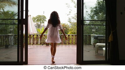 Girl Go Out To Terrace Stretching Arms Back Rear View, Enjoy Morning View Of Tropic Forest