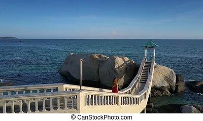 Girl Goes down on Bridge against Stunning Seascape -...