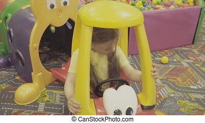 Girl goes for a drive by car - girl riding a toy car