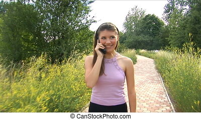 Girl goes on a footpath and speaks by phone
