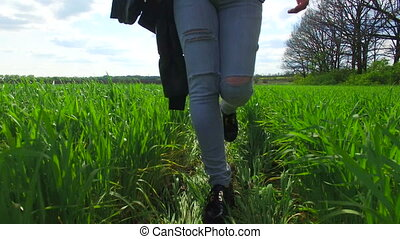 Girl goes on a green field of wheat