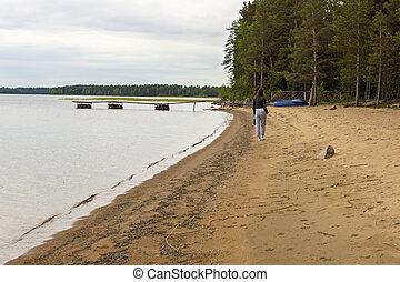 Girl goes on coast of lakeside