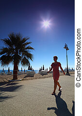 Girl goes on path with palms on empty sandy beach with folded umbrellas and sunbeds, burning sun and cloudless sky